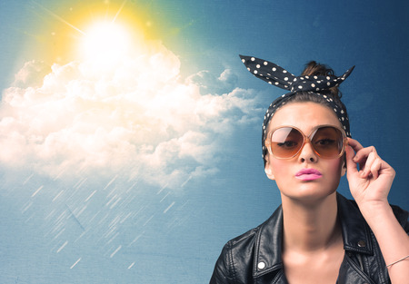 good and bad: Young person looking with sunglasses at clouds and sun concept on blue background