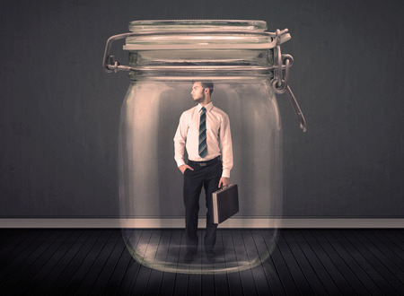 suffocating: Businessman trapped into a glass jar concept on background