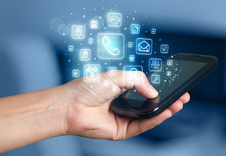 mobile device: Hand holding smartphone with glowing mobile app icons Stock Photo