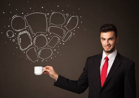Businessman standing and holding a white cup with drawn speech bubbles coming out of the cup photo