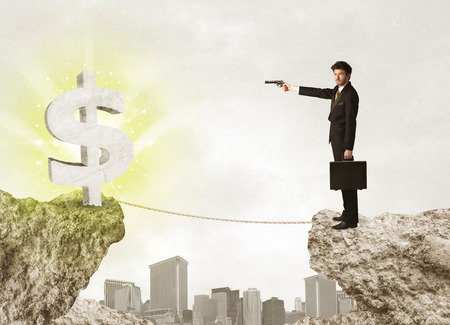bridging the gap: Businessman standing on the edge of mountain with a shining dollar mark on the other side