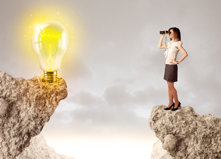bridging the gap: Businesswoman standing on the edge of rock mountain with an idea bulb on the other side