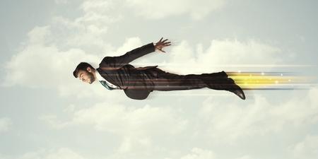 Boldog üzletember repülő gyors az égen felhők között koncepció
