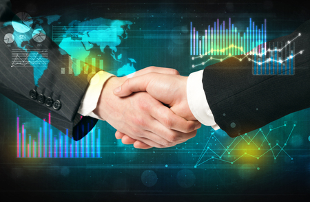 global partnership: Handshake with charts and diagrams background