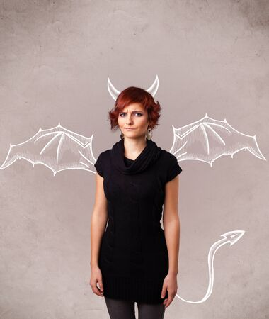 dangerous woman: Young nasty girl with devil horns and wings drawing Stock Photo