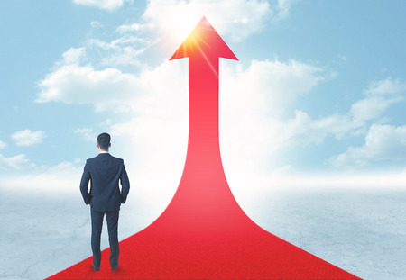 Concept of the road to success with a businessman standing on a red arrow photo