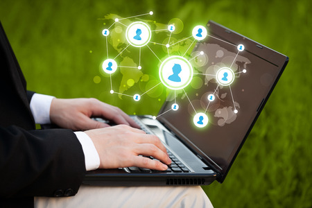 network marketing: Close up of hand with laptop and social media network icons