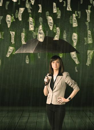 Businesswoman standing with umbrella in dollar bill rain concept on background photo
