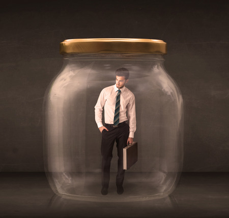 suffocating: Businessman shut into a glass jar concept on background Stock Photo