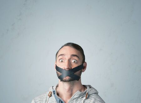 sellotape: Young man with taped mouth. Isolated on gray background