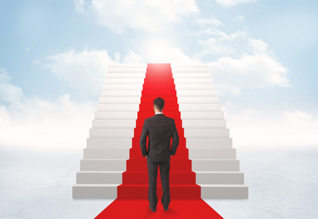 Businessman looking at stairs to heaven photo