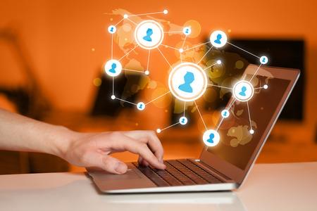 redes de mercadeo: Cierre plano de la mano con el portátil y sociales iconos de la red de medios de comunicación