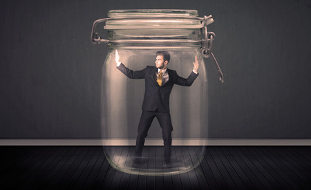 trapped: Businessman trapped into a glass jar concept on background