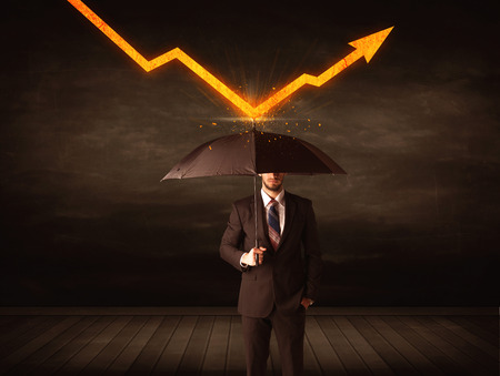 Businessman standing with umbrella keeping orange arrow concept on background Stock Photo