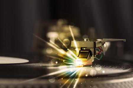 auriculares dj: Reproductor de música jugando vinilo con líneas resplandor comming del concepto de la aguja en el fondo Foto de archivo