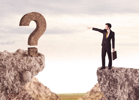 bridging the gap: Businessman standing on the edge of mountain with a rock question mark on the other side Stock Photo