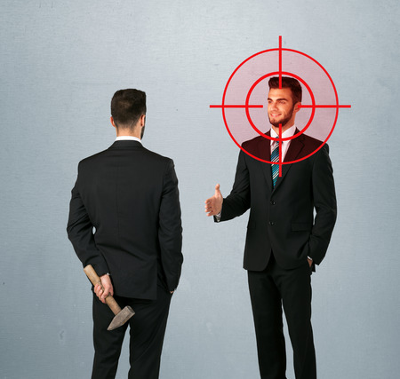 unethical: Ruthless businessman handshake with a hiding weapon and a head target point