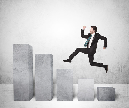 jump: Successful business man jumping over charts on background concept Stock Photo
