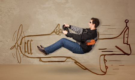 funny people: Funny pilot driving a hand drawn airplane on the wall concept