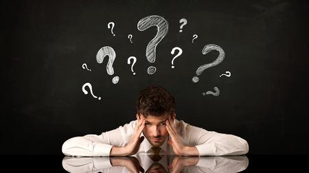 Deprimiert Geschäftsmann sitzt unter Fragezeichen Standard-Bild - 39777036