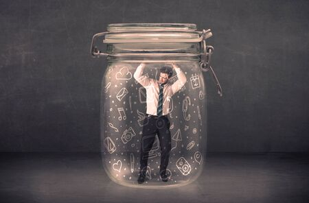 suffocating: Business man captured in glass jar with hand drawn media icons concept on background