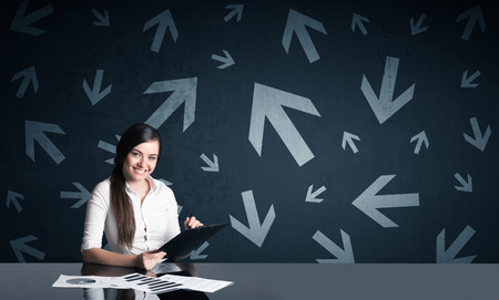 indecision: Successful businesswoman with arrows in background Stock Photo