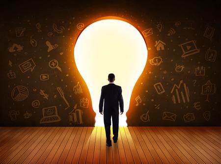 gerente: Hombre de negocios mirando bombilla de luz brillante en el concepto de la pared