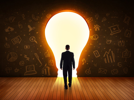 Business man looking at bright light bulb in the wall concept Stockfoto