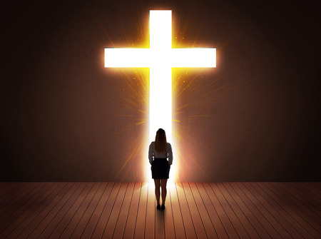 Woman looking at bright cross sign concept photo
