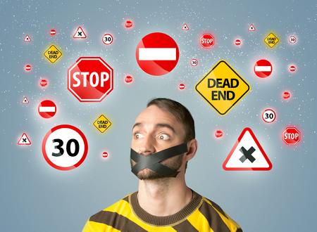 guardar silencio: Hombre joven con las señales de tráfico y la boca con cinta alrededor de la cabeza Foto de archivo