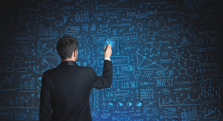 Businessman drawing business schemes on glass wall photo
