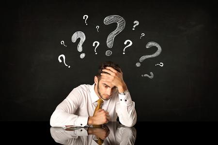 signo de interrogacion: Hombre de negocios deprimido sentado bajo signos de interrogación Foto de archivo