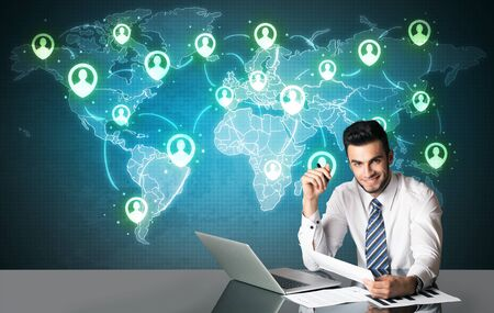 Businessman sitting at table with social media connection symbols on the world map photo