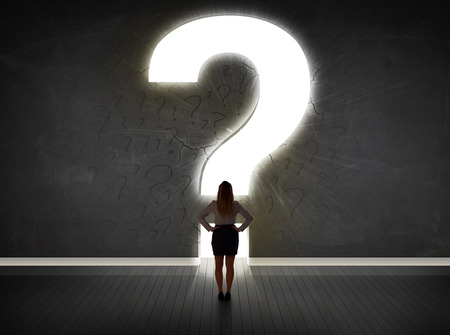 Business woman looking at wall with a bright question mark concept Imagens