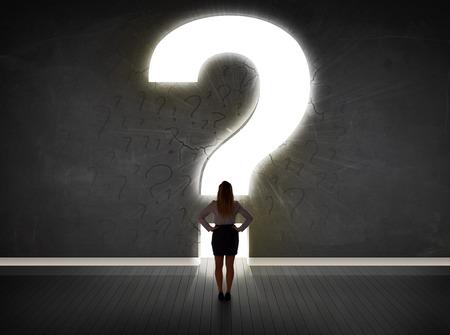 persona confundida: Mujer de negocios que mira la pared con un concepto de signo de interrogaci�n brillante Foto de archivo