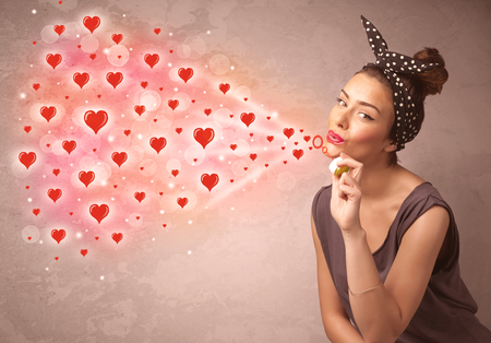 Pretty young girl blowing valentine red heart symbols photo
