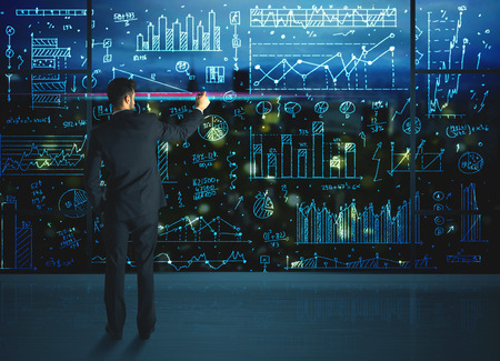 information analysis: Businessman drawing business statistics on glass wall