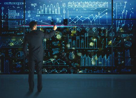 GERENTE: Dibujo estadísticas de las empresas sobre la pared de vidrio del hombre de negocios
