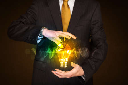 shining light: Businessman holding a shining light bulb in front of his body Stock Photo