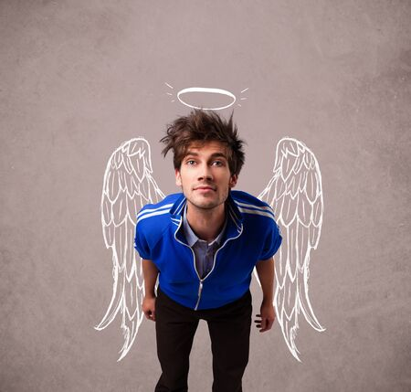 Young man with angel illustrated wings on grungy background photo