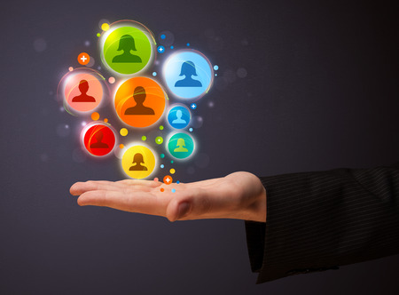 network concept: Businessman holding colorful social network icons in his hand
