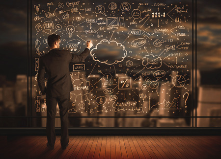 Businessman drawing business plan on glass window with bokeh background photo