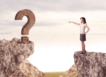 bridging the gaps: Businesswoman standing on the edge of mountain with a rock question mark on the other side Stock Photo