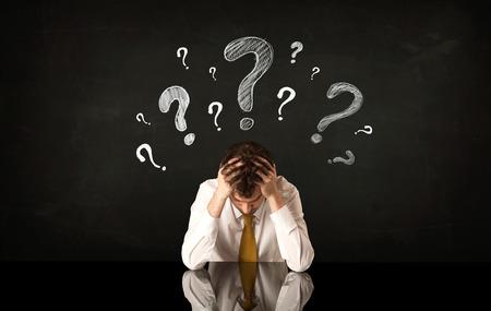 Uomo d'affari depresso seduto sotto un punto interrogativo Archivio Fotografico - 41460007