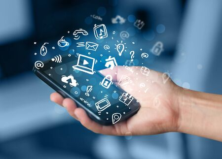 smartphone in hand: Hand holding smartphone with media icons and symbol collection Stock Photo