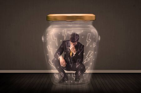 suffocating: Businessman inside a glass jar with lightning drawings concept on background