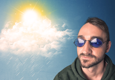 person looking: Young person looking with sunglasses at clouds and sun concept on blue background