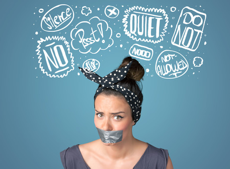 Young woman with taped mouth and white drawn thought clouds around her head photo