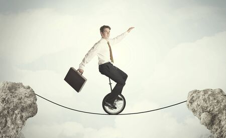 reckless: Brave business man riding an mono cycle between cliffs concept
