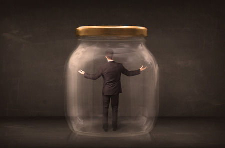 Businessman shut into a glass jar concept on background Stock Photo